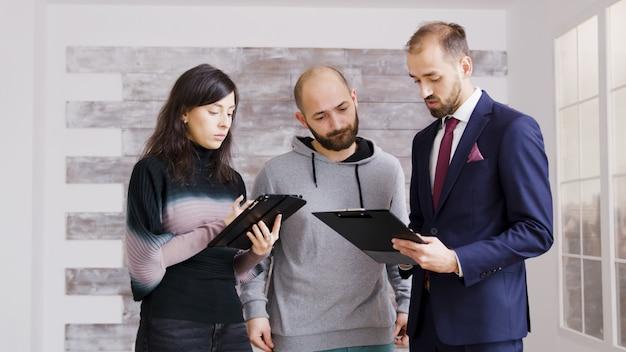 Agente immobiliare in giacca e cravatta che parla di finanze con i clienti per acquistare un nuovo appartamento. broker con clienti in appartamento vuoto.
