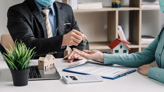 L'agente immobiliare e il cliente accettano il contratto di compravendita della casa hanno consegnato con successo la chiave.