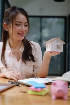 Un agente immobiliare mostra il modello della casa ai clienti interessati all'acquisto di un'assicurazione sulla casa. il concetto di assicurazione casa e proprietà.