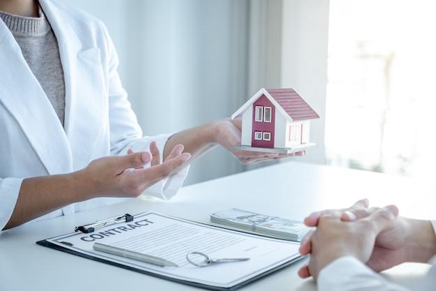 L'agente immobiliare spiega il contratto d'affari, l'affitto, l'acquisto, il mutuo, un prestito o l'assicurazione sulla casa all'acquirente femminile.