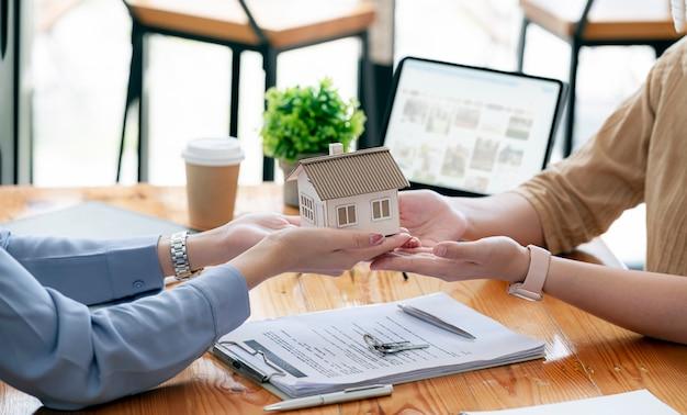 Un agente immobiliare dà la casa al cliente di un nuovo proprietario dopo aver completato la firma del contratto di locazione.