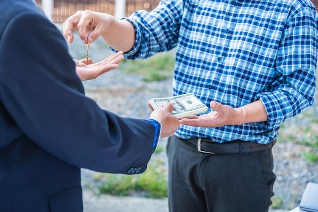 Agente immobiliare che fornisce le chiavi della casa davanti al supporto della casa con l'architetto