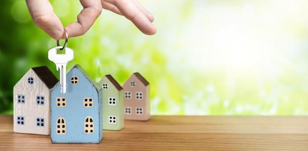 Mano dell'agente immobiliare con chiave e case in miniatura su sfondo verde con luce solare. immobiliare, compra vendita casa, concetto di mutuo