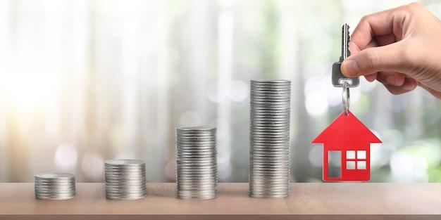 Agente immobiliare che consegna una casa chiavi in mano e monete