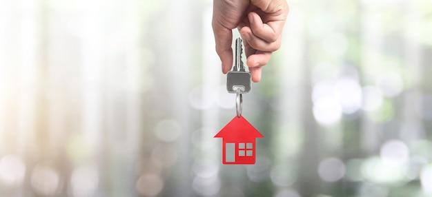 Agente immobiliare che consegna le chiavi di una casa in mano e le monete