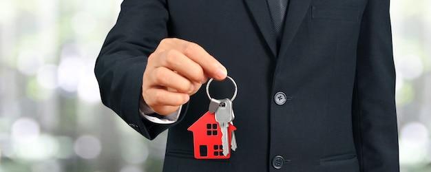 Agente immobiliare che consegna le chiavi di una casa in mano