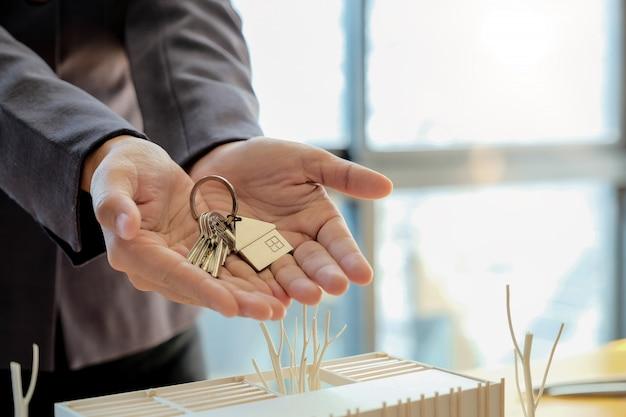 Agente immobiliare che consegna le chiavi di casa con il modulo di richiesta di mutuo approvato e offre la stretta di mano