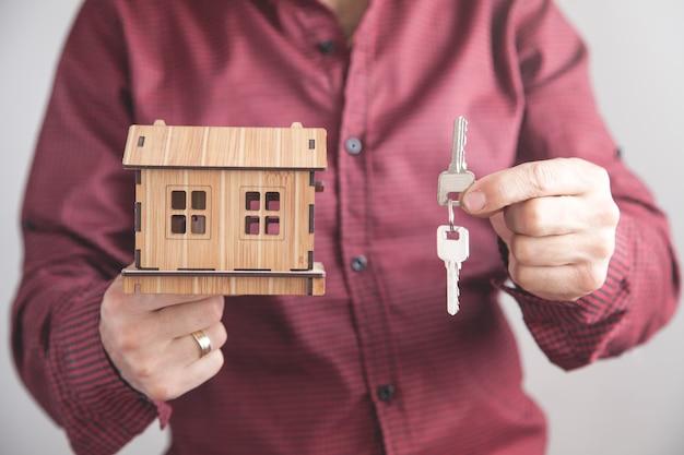 Agente immobiliare che tiene le chiavi di casa con un modello di casa in ufficio concetto di affari