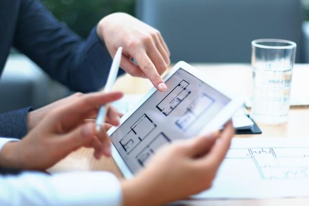 Agente immobiliare che mostra i piani della casa su tablet elettronico