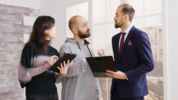 Agente immobiliare che parla con una coppia e tiene documenti contratto di proprietà in un nuovo appartamento.