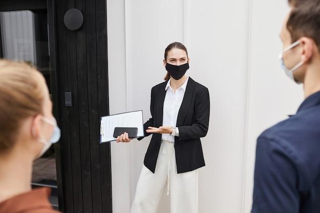 Agente immobiliare che indossa la maschera durante il tour della casa