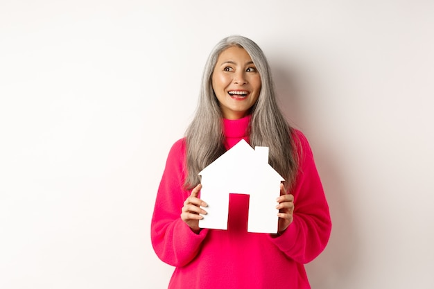 Immobiliare. bella donna adulta asiatica con i capelli grigi, sognando di acquistare proprietà, mostrando il modello della casa di carta e guardando l'angolo in alto a sinistra, sfondo bianco