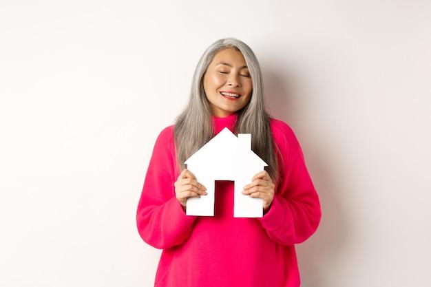 Immobiliare. bella signora asiatica sognante che abbraccia il modello di casa di carta con gli occhi chiusi, sorridendo mentre sogna di acquistare un appartamento, in piedi su sfondo bianco.