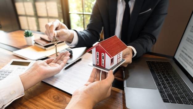 Agente immobiliare o agente di vendita che fornisce consulenza al cliente sull'acquisto del documento di accordo del segno di casa
