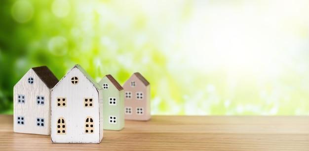 Immobiliare, compra vendita casa, concetto di mutuo. case in miniatura su sfondo verde con la luce del sole.