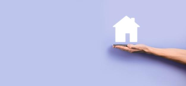 Concetto di bene immobile, uomo d'affari che tiene un'icona della casa. casa a portata di mano. concetto di assicurazione e sicurezza della proprietà. gesto protettivo dell'uomo e simbolo della casa