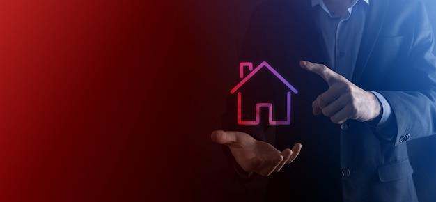 Concetto di bene immobile, uomo d'affari che tiene un'icona della casa. proteggere il gesto dell'uomo e il simbolo della casa.