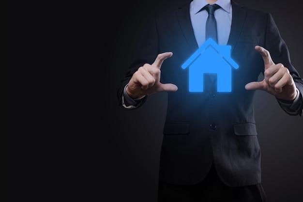 Concetto di bene immobile, uomo d'affari che tiene un'icona della casa. casa a portata di mano. concetto di assicurazione e sicurezza della proprietà. gesto protettivo dell'uomo e simbolo della casa.