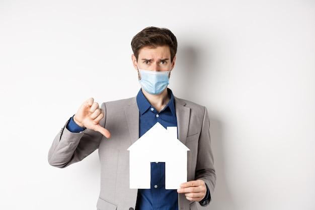 Concetto di proprietà immobiliare e covid-19. ragazzo deluso in maschera medica e vestito che mostra il ritaglio della casa di carta con il pollice verso il basso, lamentandosi dell'agenzia, sfondo bianco.