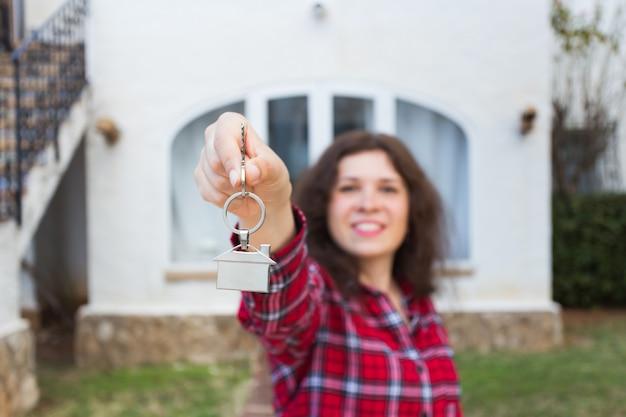Concetto di bene immobile e proprietà - felice giovane donna davanti alla nuova casa con le nuove chiavi di casa