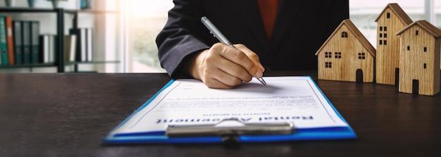 Concetto del contratto di firma del proprietario del bene immobile, della proprietà e della casa, modello della piccola casa di legno sul tavolo dell'ufficio con la mano del compratore della donna firma sul contratto di affitto carta da affittare sopra menzionata residenza