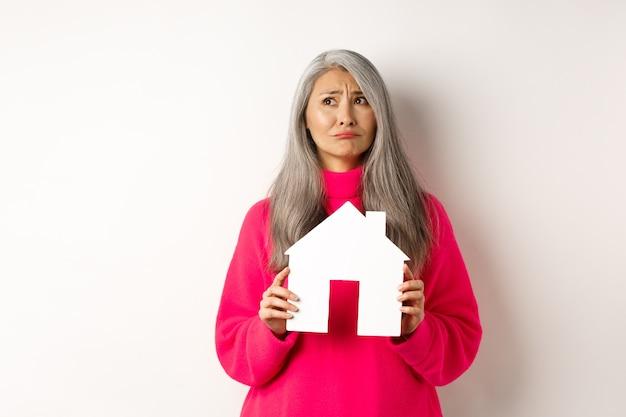Donna anziana asiatica triste del settore immobiliare che sogna la propria proprietà con un modello di casa di carta e grimaci...