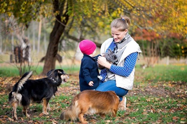 Persone di famiglia reali, bambini e adulti con molti animali domestici, si divertono all'aperto nel cortile della fattoria di campagna