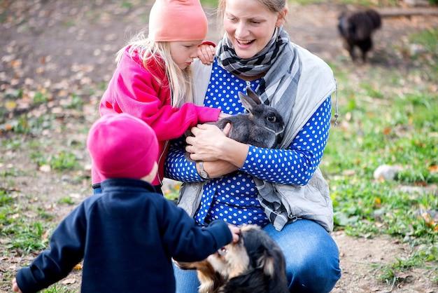 Persone di famiglia reali, bambini e adulti con molti animali domestici, si divertono all'aria aperta
