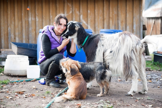 La vera contadina con molti animali domestici si diverte all'aria aperta nel cortile della fattoria di campagna