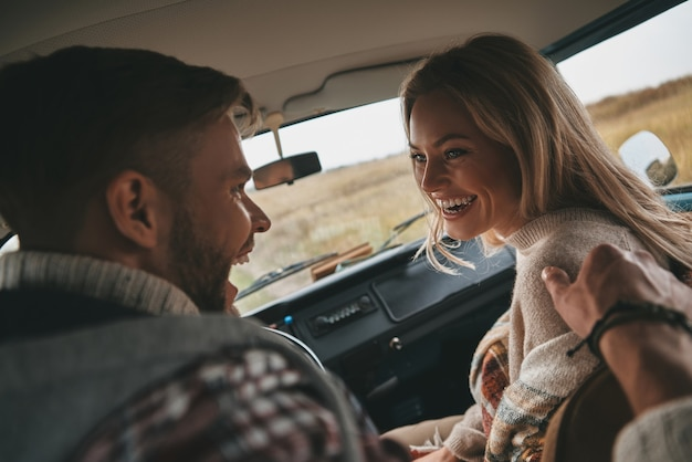 Vero amore. felice coppia giovane ridere seduti sui sedili del passeggero anteriore in stile retrò mini van