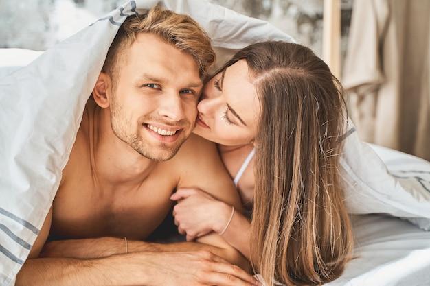 Vero amore. gentile ragazza bruna che tiene gli occhi chiusi mentre bacia il suo ragazzo, sdraiata insieme a letto
