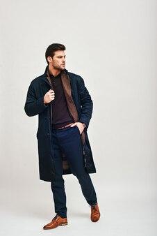 Vero macho elegante uomo dai capelli scuri in piedi e distoglie lo sguardo isolato su sfondo bianco