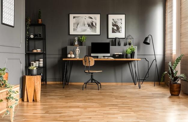 Foto reale dell'interno spazioso dell'ufficio di avvio con una sedia singola su una scrivania in legno con computer e piante in piedi contro il muro nero con modanatura