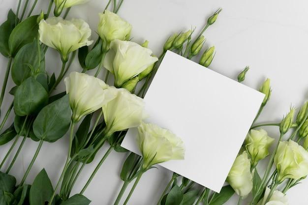 Foto reale. mockup di biglietti d'invito quadrati con fiori di eustoma. vista dall'alto con copia spazio, sfondo grigio chiaro. modello per il branding e la pubblicità