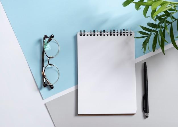 Foto reale, modello di blocco note mockup con marchio di cancelleria per posizionare il tuo disegno, isolato su sfondo grigio chiaro, blu, foglie di palma, ombra.