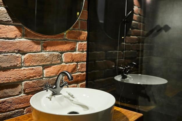 Foto reale di un lavabo in un bagno interno con muro di mattoni e specchio Foto Premium