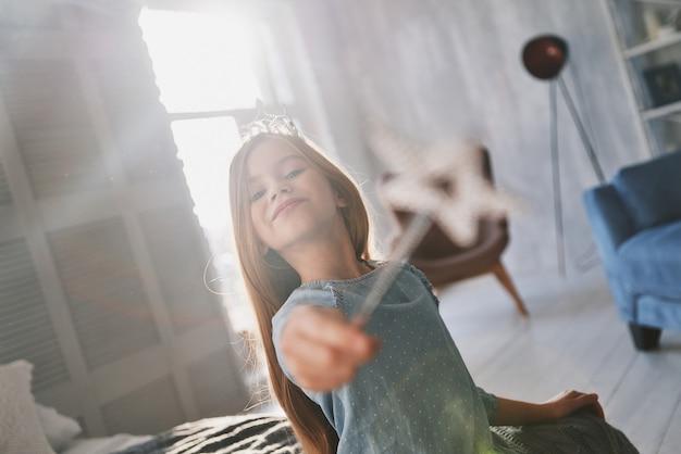 Vera principessa. bambina carina che gioca con una bacchetta magica mentre passa il tempo a casa