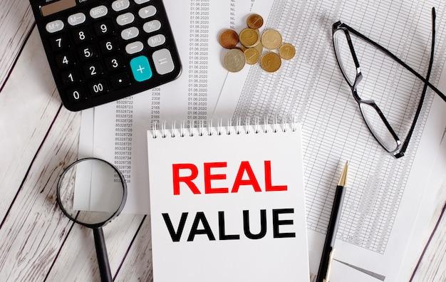 Valore reale scritto in un blocco note bianco vicino a una calcolatrice, contanti, occhiali, una lente d'ingrandimento e una penna