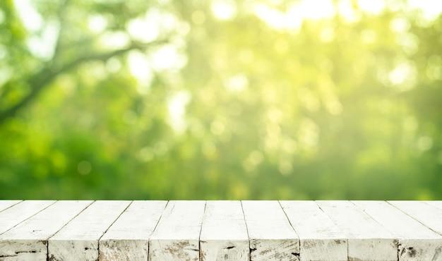 Struttura del piano d'appoggio in vero legno sul fondo del giardino dell'albero di foglia