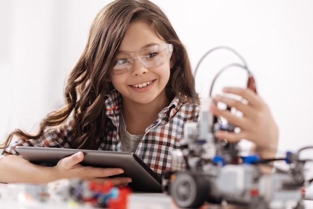Realizzando la mia idea scientifica. ragazza allegra sorridente astuta che si siede nell'aula di scienze e che utilizza dispositivi durante gli studi