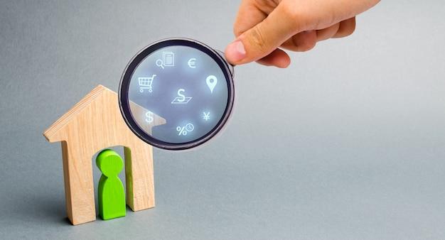 L'agente immobiliare esamina le case attraverso una lente d'ingrandimento