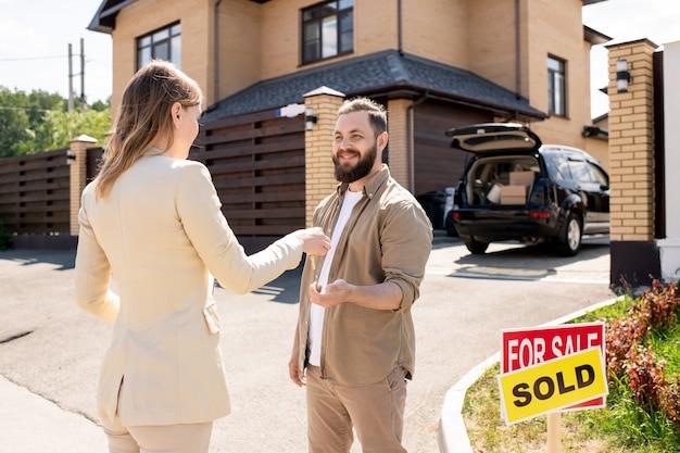 Agente immobiliare che passa la chiave all'acquirente