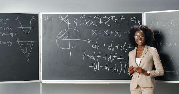 Parte posteriore del giovane insegnante femminile afroamericano di matematica o fisica che scrive formule sulla lavagna con il gesso. ritratto di donna allegra tutor girando alla telecamera e sorridendo felicemente. vista posteriore.