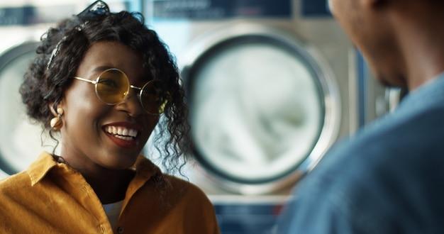 Parte posteriore della ragazza di riunione del giovane tipo afroamericano e abbracciare alla stanza di servizio di lavanderia. chiuda su delle coppie di amici che si incontrano, che parlano e che sorridono nel lavatoio mentre lavorano le lavatrici.