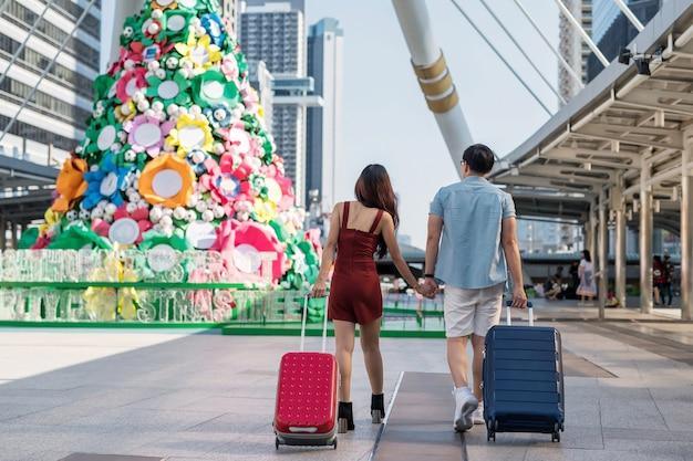 La parte posteriore della coppia di turisti asiatici si tiene per mano mentre cammina e tira due valigie da viaggio nella moderna città urbana