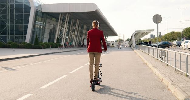 Posteriore su allegro giovane uomo bello caucasico in cuffie che guidano scooter elettrico e ascolto di musica all'aperto al grande edificio urbano. costruzione moderna. vista posteriore. ragazzo felice alla moda divertendosi.