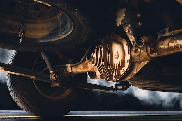 Albero di trasmissione posteriore con sporco di camioncino sulla strada asfaltata e fumo di notte