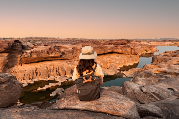 Parte posteriore dell'esploratore donna seduta sul canyon di roccia naturale alla sera a sam phan bok del grand canyon in thailandia