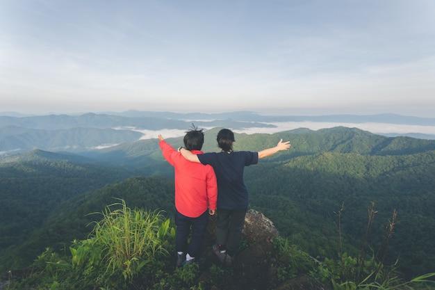 La parte posteriore dell'amore delle coppie felici sta sulla vista di sguardo della montagna superiore alla luce del mattino.