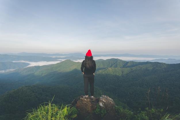La parte posteriore della donna felice sta sulla vista di sguardo della montagna superiore con la foschia e la nuvola